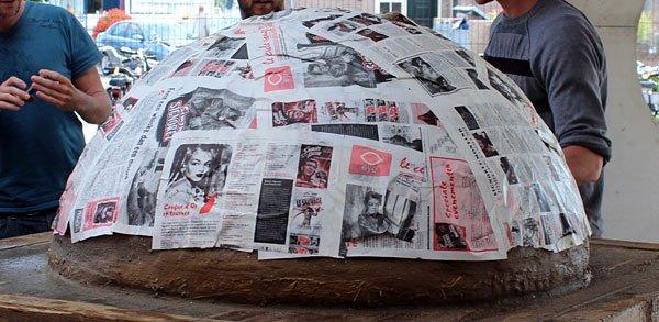 Het bedekken van de zandbol met natte kranten om vermenging met leem te voorkomen